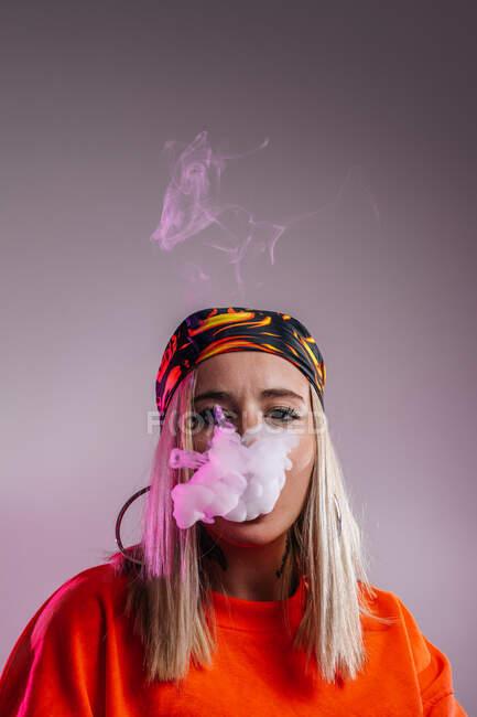 Fresco femminile in abito street style fumare e sigaretta ed espirare fumo attraverso il naso su sfondo viola in studio con illuminazione al neon rosa — Foto stock