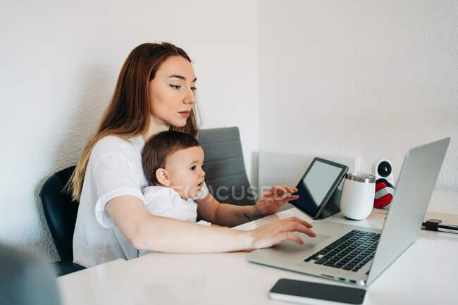 Сфокусована молода мати працює на ноутбуці, тримаючи цікавого малюка, дивлячись смішне відео на планшеті, сидячи разом за столом у світлій кімнаті. — стокове фото
