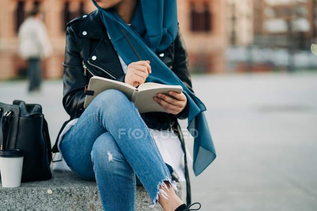 Cultiver femme musulmane dans le hijab écrit dans un journal tandis que assis sur la rue de la ville et regardant loin — Photo de stock