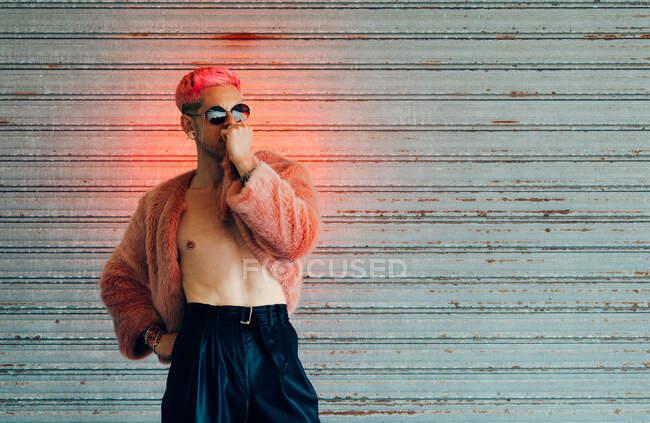 Joven gay en gafas de sol modernas y elegante chaqueta de piel con pelo rosa contra la pared gris - foto de stock