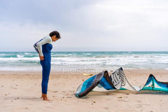 Vista lateral do kiter fêmea descalço no wetsuit que está na praia arenosa do oceano contra o kite do poder sob o céu nublado — Fotografia de Stock