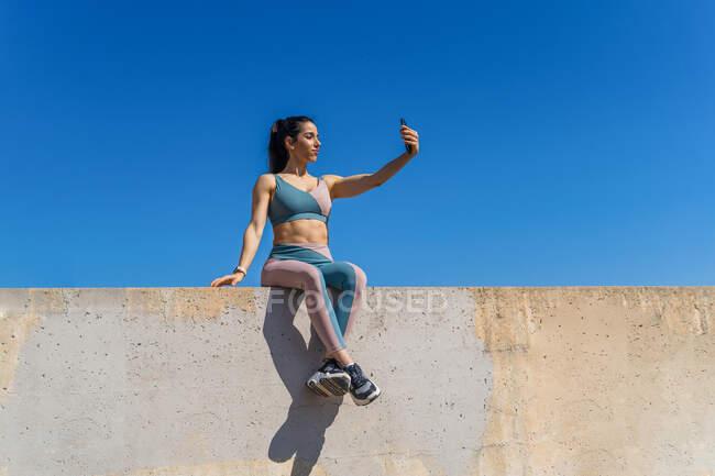 Самоуверенная спортсменка со скрещенными ногами делает автопортрет на мобильном телефоне, сидя на бетонном заборе под голубым небом — стоковое фото