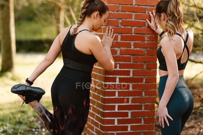 Спортсменка с подружкой в спортивной одежде тренируется с поднятыми ногами на тротуаре в городе в солнечный день — стоковое фото