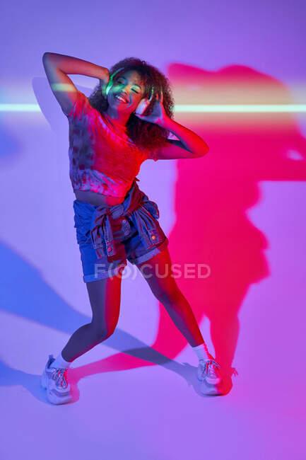 Mujer afroamericana feliz de cuerpo completo en pantalones cortos escuchando música favorita en auriculares y bailando con los ojos cerrados en luces de neón en el estudio - foto de stock
