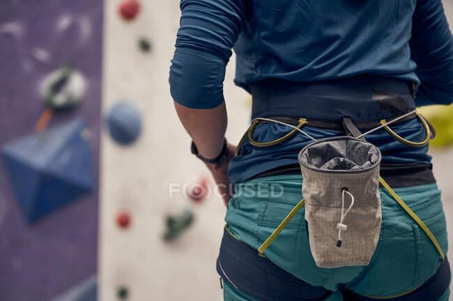Visão traseira do montanhista anônimo no cinto de segurança em pé no moderno ginásio de pedregulhos antes de escalar a parede — Fotografia de Stock
