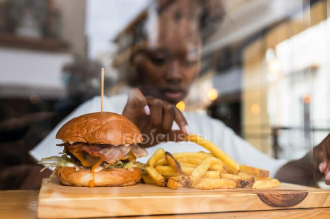A través de la pared de vidrio borrosa hembra afroamericana comiendo deliciosas papas fritas y deliciosa hamburguesa servida en tablero de madera en la mesa alta en el restaurante de comida rápida - foto de stock