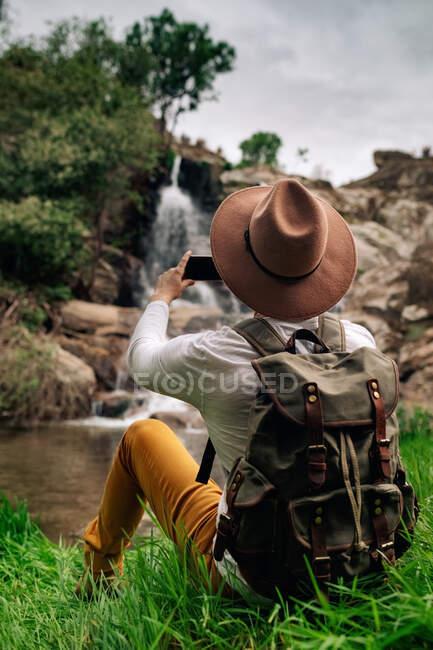 Voltar ver viajante masculino sem rosto em desgaste casual e chapéu tirar fotos no smartphone de cascata rápida caindo de formações rochosas na natureza verdejante — Fotografia de Stock