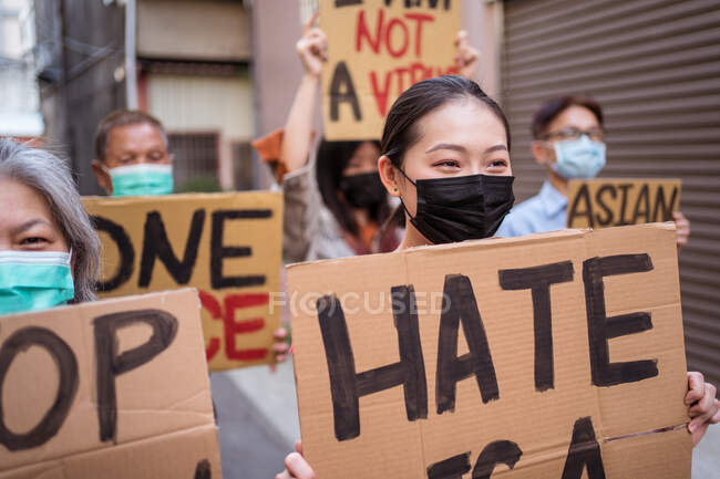 Ethnic activists with I Am Not A Virus and One Race inscriptions on placards during Stop Asian Hate movement in town — стокове фото