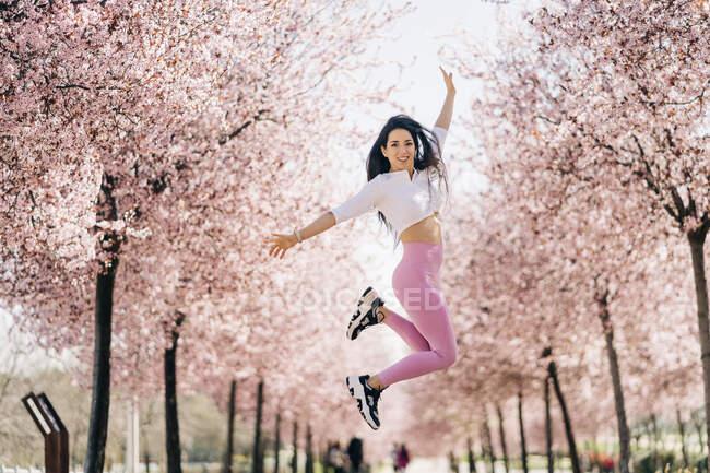 Вид сбоку на улыбающуюся спортсменку в спортивной одежде, прыгающую между цветами вишни, глядя в камеру — стоковое фото