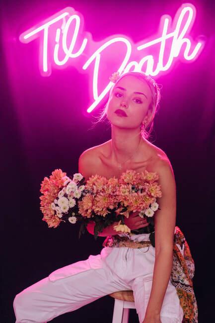 Atractiva joven mujer desnuda con hombros en pantalones blancos con ramo de flores frescas y coloridas sentado en el taburete contra la inscripción de neón brillante en el estudio oscuro - foto de stock