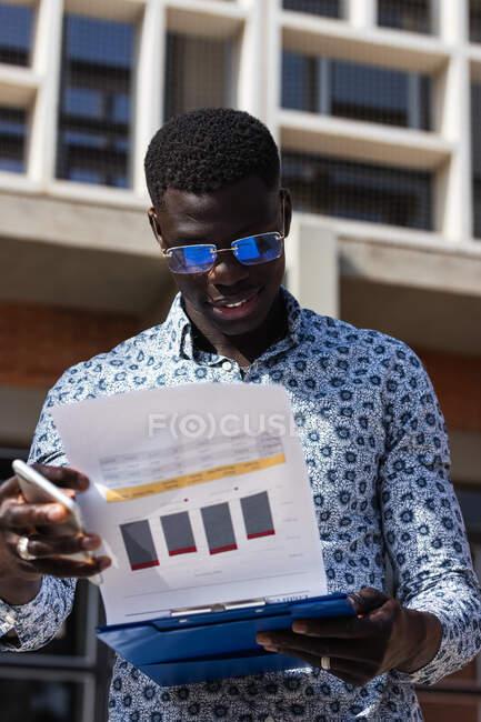 Молодий розумний афроамериканський підприємець у окулярах з дошкою для спостереження за картами на папері в місті. — стокове фото