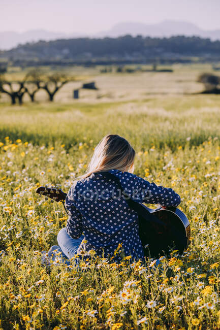 Back view of thoughtful unrecognizable hipster woman sitting on a meadow in the countryside playing guitar during summer sunlight — Stock Photo
