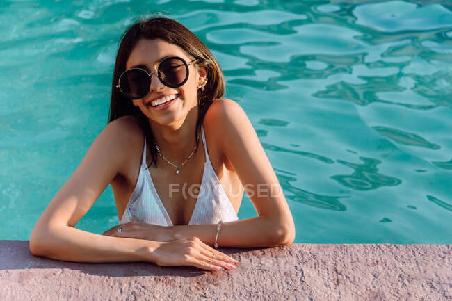 Young cheerful ethnic female tourist in swimwear and accessories leaning with hands on poolside in sunlight — Stock Photo