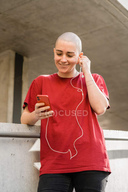 Young homosexual female in t shirt and earphones with cellphone looking at screen while listening to music — Stock Photo