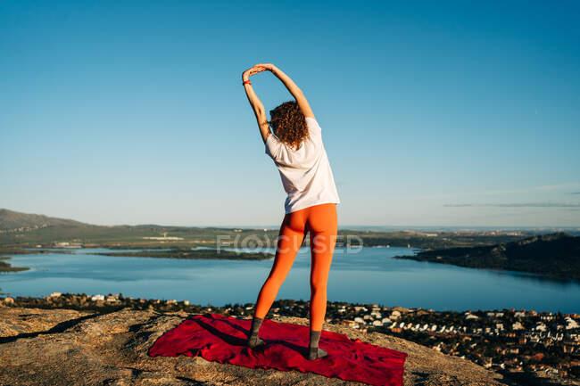 Вид сзади на неузнаваемую молодую женщину в активной одежде, растягивающуюся тело, стоя на скалистом холме во время занятий йогой под безоблачным голубым небом — стоковое фото