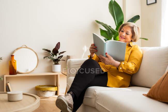 Женщина средних лет отдыхает на диване и читает интересную историю, наслаждаясь выходными дома — стоковое фото