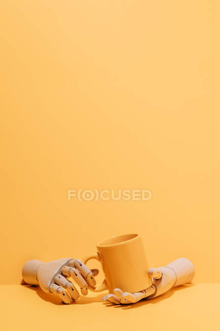 Creative ornamental wooden hand holding colorful mug on yellow background in studio — стокове фото