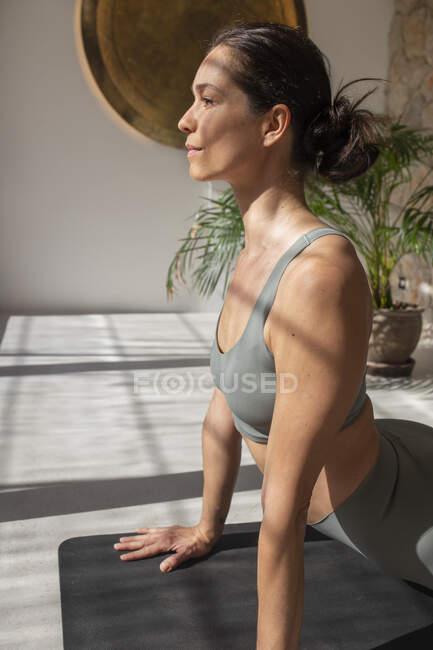 Вид сбоку мирной женщины в активном костюме, практикующей йогу в Бхуджангасане, растягивающей тело и отводящей взгляд — стоковое фото
