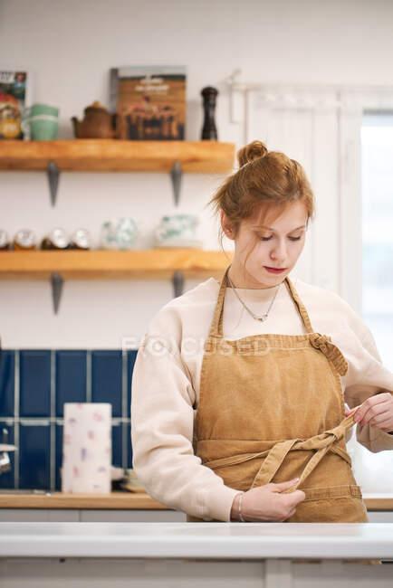 Молода самовпевнена жінка дивиться вниз на стіл у світлому домі. — стокове фото