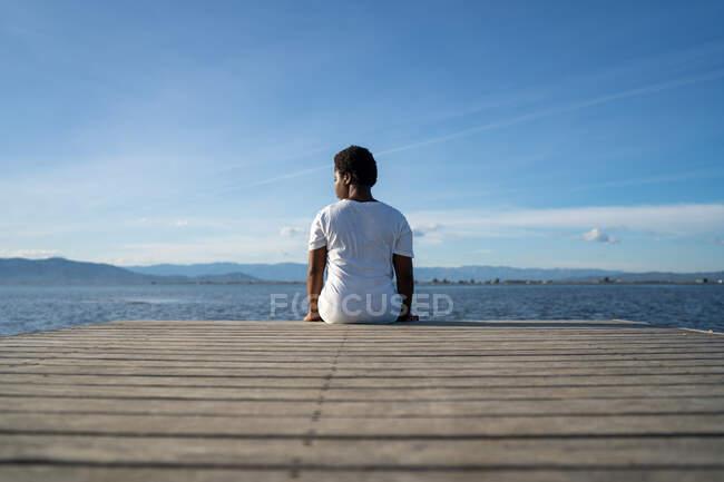 Vista posterior mujer afroamericana anónima en ropa blanca sentada en un muelle de madera cerca de un vasto lago ondulado bajo un cielo azul claro en verano - foto de stock