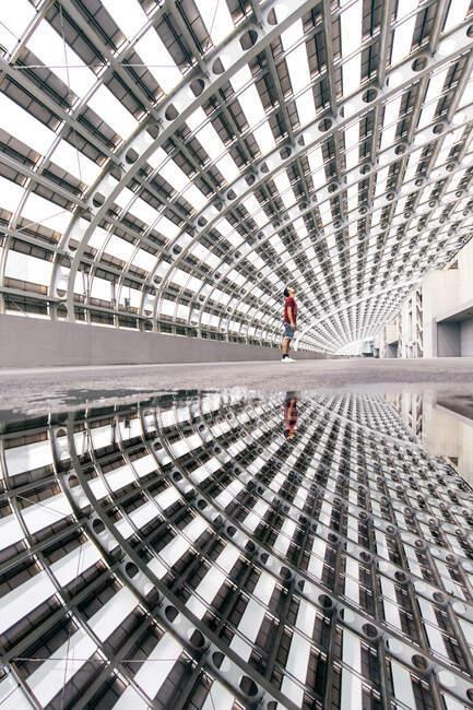 Homem irreconhecível em pé em passagem de vidro incomum com paredes curvilíneas geométricas refletindo em poça de água na cidade urbana — Fotografia de Stock