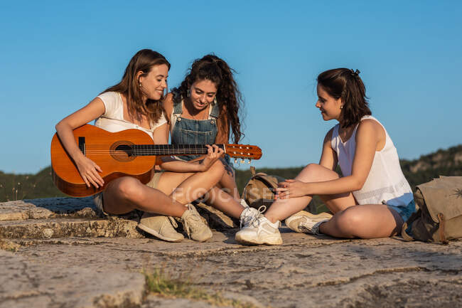 Group of female hikers sitting on hill in highlands while playing acoustic guitar and singing songs — Stock Photo