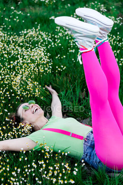 Side view joyful young female wearing bright outfit lying on lush grass with raised legs in countryside — Stock Photo