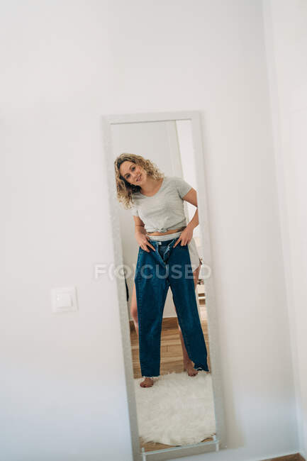 Full body of positive young female with curly blond hair looking in mirror while trying on stylish jeans at home — Fotografia de Stock