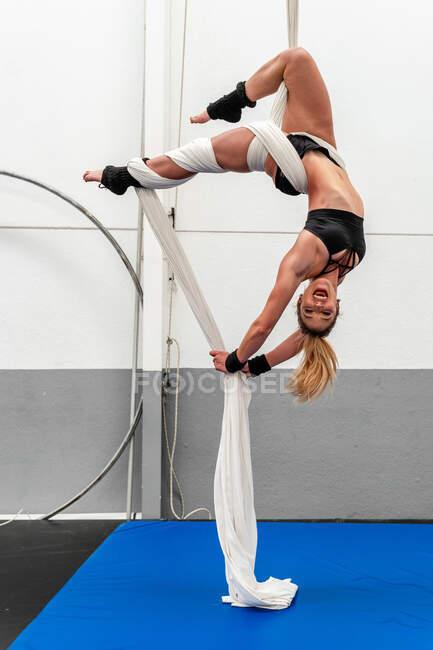 Полная длина счастливый подходит гибкая спортсменка в активации вверх ногами практикуя воздушные упражнения на шелка в современном оборудованном спортивном клубе — стоковое фото