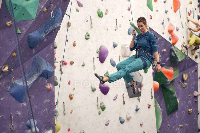 Вид сбоку женщины-альпинистки, висящей на технике безопасности во время тренировок в современном боулдеринговом клубе — стоковое фото