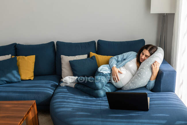 Розкішна вагітна жінка лежить на зручному дивані і дивиться смішне відео на нетбуку, відпочиваючи вдома. — стокове фото