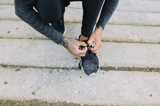 Atleta sem rosto com a mão tatuada vestindo roupas esportivas pretas totais e amarrando atacadores de tênis no pavimento — Fotografia de Stock