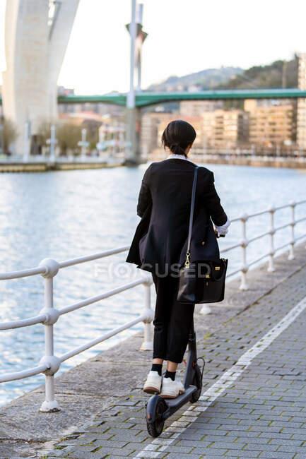 Vista trasera de empresaria étnica irreconocible en ropa formal montando scooter eléctrico en la pasarela de la ciudad - foto de stock