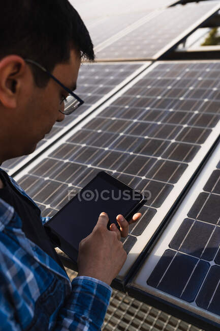 Concentrated ethnic male technician in checkered shirt browsing tablet while standing near photovoltaic panel located in modern solar power farm - foto de stock