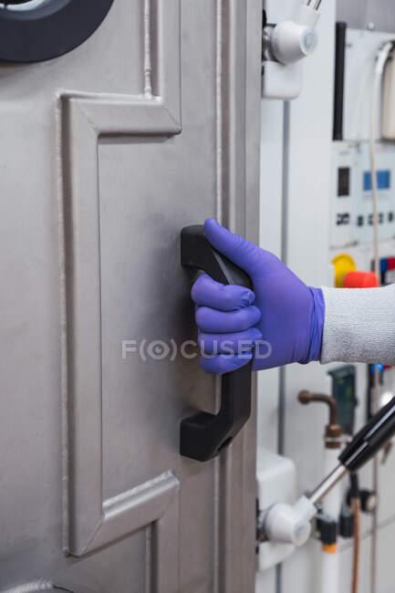 Безликий робітник у захисних латексних рукавичках відчиняє двері закритого об'єкта біобезпеки під час роботи в сучасній обладнаній лабораторії. — стокове фото