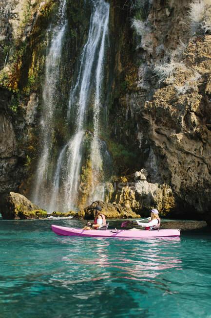 Vista lateral viajeros anónimos con remos flotando en agua de mar turquesa cerca de la cascada escénica en un día soleado en Málaga España - foto de stock