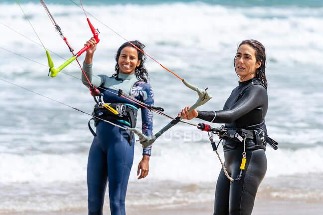 Atleta multietnica in muta con kiteboard e barre di controllo che si guardano sulla costa sabbiosa contro l'oceano schiumoso — Foto stock