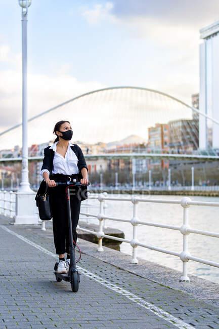 Етнічні жінки-підприємці в тканинній масці і офіційному одязі їздять на електричному скутері, дивлячись на дорогу в місті під час пандемії коронавірусу. — стокове фото