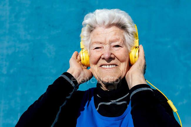 Mujer anciana encantada con pelo gris y auriculares amarillos disfrutando de canciones mientras escucha música sobre fondo azul en el estudio - foto de stock
