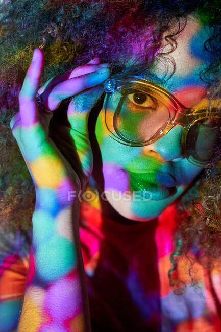 Portrait of attractive young African American female in stylish sunglasses looking at camera while standing in neon lights — Stock Photo