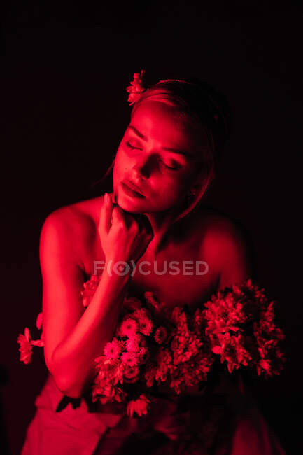 Attractive young bare shouldered female in white pants with bouquet of fresh colorful flowers sitting on stool against bright neon light in dark studio with eyes closed — Stock Photo
