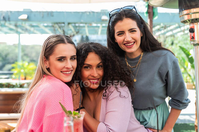 Smiling young multiracial female friends in casual clothes embracing and looking at camera while spending sunny day together on outdoor restaurant terrace — стокове фото