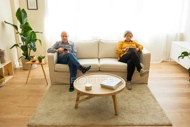 Высокий угол зрения зрелого мужчины, использующего смартфон, и женщины средних лет, просматривающей планшет, сидя на диване в гостиной дома — стоковое фото