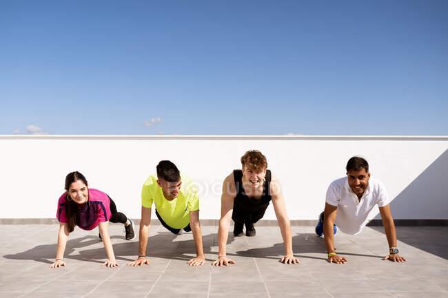 Полная группа весёлых молодых многорасовых спортивных друзей в спортивной форме, занимающихся досками на коврике во время тренировки на террасе против безоблачного голубого неба — стоковое фото