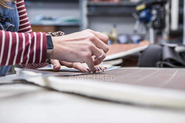 Cortar esgoto feminino irreconhecível fazendo pedaço de pano enquanto trabalhava na oficina e criando estofos para assentos de motocicleta — Fotografia de Stock
