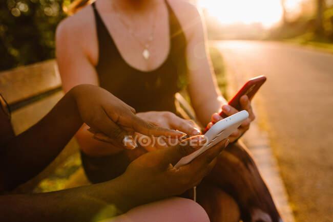Cultivo multirracial atletas femeninos en ropa deportiva sentado en el banco en el parque y el uso de teléfonos móviles juntos después del entrenamiento al atardecer - foto de stock