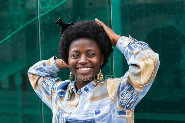 Портрет молодої афроамериканської жінки з традиційним гребінцем на африканському волоссі, одягненої в стильний неформальний одяг, посміхаючись щасливо, стоячи біля скляної стіни з відображенням міської вулиці. — стокове фото