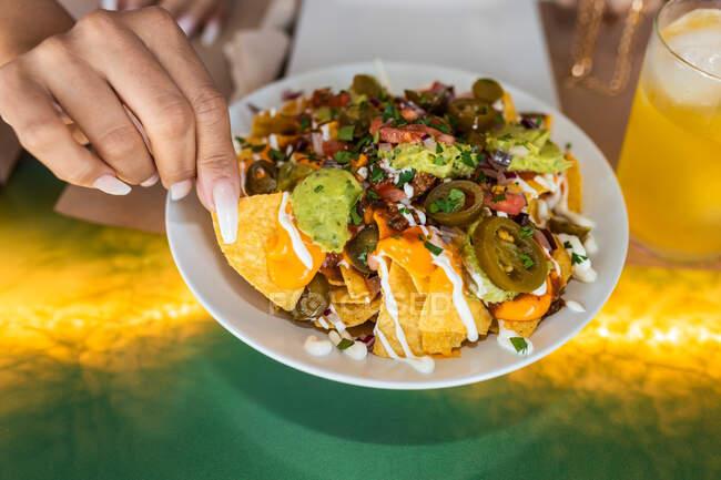 Vista superior de la cosecha irreconocible hembra comiendo deliciosos nachos mexicanos tradicionales con chile jalapeño cubierto con queso y salsa de guacamole sentado a la mesa en el restaurante - foto de stock