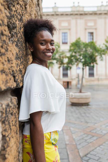 Портрет привабливої афроамериканської жінки, що стоїть в історичному районі міста в теплий день весни і дивиться на камеру — стокове фото