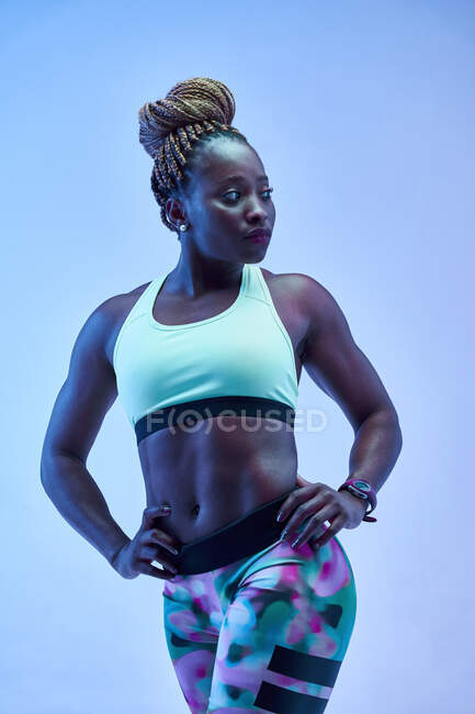 Muscular African American female athlete with sweaty body showing biceps on blue background — Stock Photo